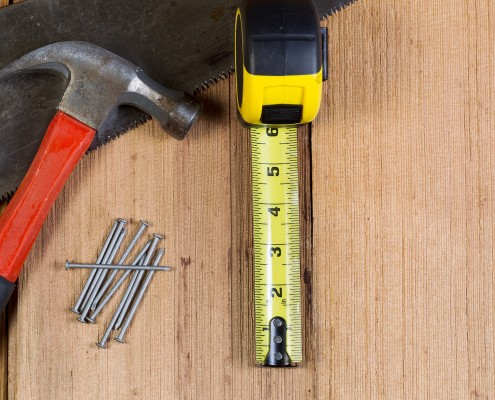 Top view of home repair tools consisting of wood saw, hammer, nails, and tape measure on cedar wooden shingles for roof