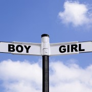 Black and white signpost with Boy and Girl on the directional arrows against a blu cloudy sky.