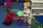 MR / Schenectady, NY Schenectady Day Nursery / private non-profit daycare center / Infant Class Babies play together with colored cube blocks. (Toddler left: boy, 1, African-American / Hispanic; infant right: boy, 10 months)  MR: Leo4, Coo4 © Ellen B. Senisi