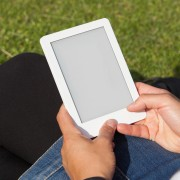 Woman reading ebook on the grass, square image